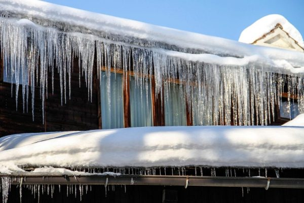Prevent Frozen Pipes and Winter Weather Damage, ice sickles hanging from gutter of home.
