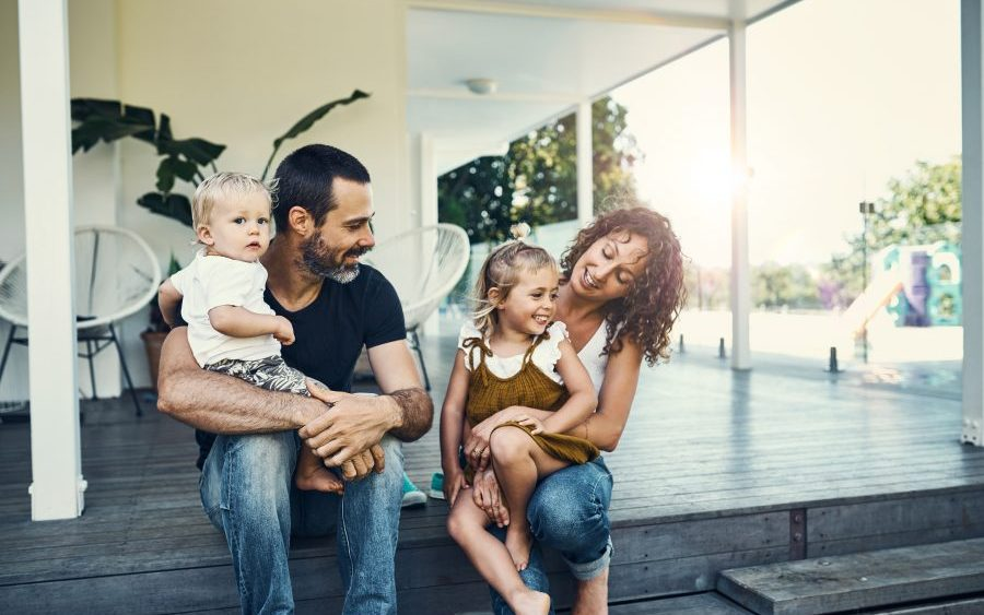 Happy young family on porch, illustrative of choosing homeowners insurance deductible.