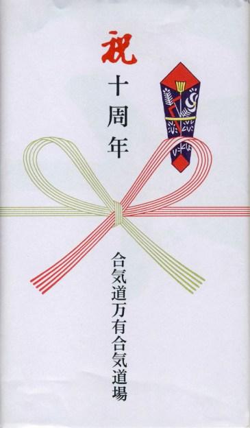 """Il tenugui viene regalato piegato e incartato con questa carta regalo tradizionale giapponese. Dall'alto verso il basso: """"10° anniversario"""". Sotto il fiocco: """"Aikido Banyuaiki Dojo""""."""