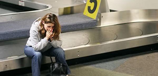 Une passagère assise sur le tapis roulant de l'aéroport attend son bagage qui ne vient pas