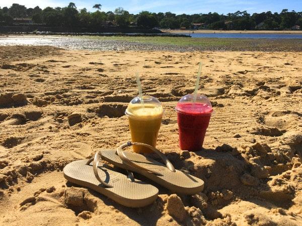 Deux verres de smoothies concoctés par Le Mango Tree et une paire de tongs posés sur la plage du lac d'Hossegor