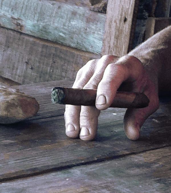 une main tenant un cigare cubain