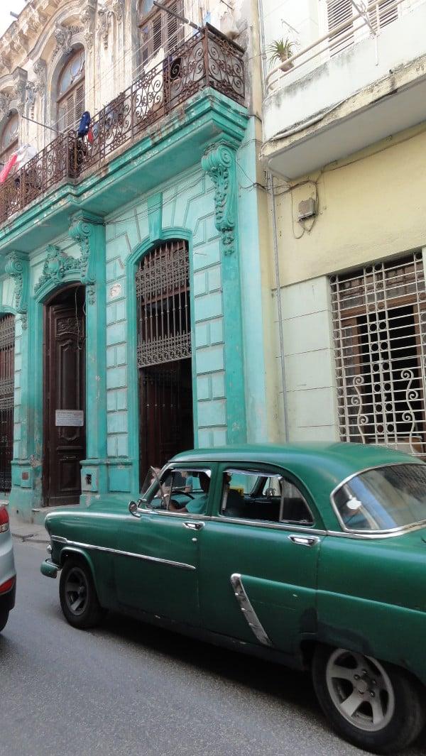 vieille voiture verte devant une façade colorée de La Havane