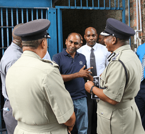 Police Social and Welfare Association president Sgt Anand Ramesar, centre, pokes fun at Police Commissioner Stephen Williams, right, during a tour of the San Fernando Police Station yesterday.