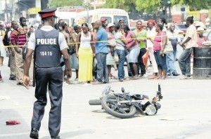 Onlookers view the crashed motorcycle that was driven by Maragh and his alleged accomplice.