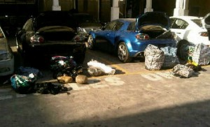 The bags and parcels of marijuana just outside the opened trunks of the three cars.