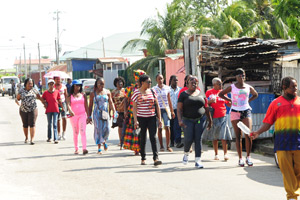 Peaceful protest: Sea Lots residents walk along Pioneer Drive yesterday on their way to the Port of Spain General Hospital in a show of solidarity for the three residents who survived Sunday's accident which claimed the lives of a mother and her two daughters. (Photo by JERMAINE CRUICKSHANK)