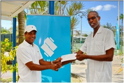 Ian DeSouza (left) presenting cheque to Dr. Raymond Forde.