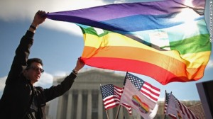George Washington University student Eric Breese waves a rainbow flag outside the US Supreme Court today, in Washington. The justices heard two cases this week related to state and federal laws restricting same-sex marriage.