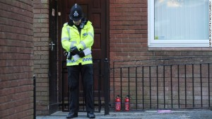 A police officer stands outside the front door of a house Atherton, England, where the body of the 14-year old girl was found.