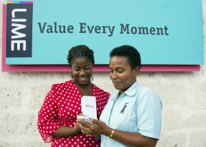 LIME's Brenda Brathwaite (right) shows Rishann Broomes the features on her new Samsung Galaxy SIII smartphone.