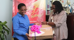 Accountant at Guardian General Insurance Limited Eurlinda Smith handing over the laptop to Precious Touch Foundation's Adorial Maxwell-Hazell.