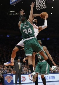 Celtics' Paul Pierce (backing) defends this shot from Knicks' Tyson Chandler.