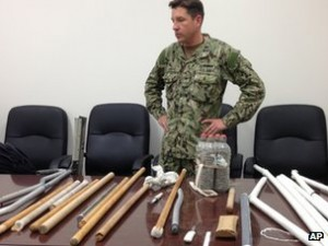 A US soldier shows confiscated items from Guantanamo Bay detainees.