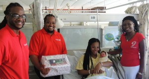 New mother, Jalyssa Alleyne, was all smiles with her new born baby girl while receiving a care package from (L-R) Digicel's Senior Engineer and President of the Sports and Social Club, Kerry Farnum; ICT Sales Executive with Digicel Business, Kevin Clarke; and Distribution Manager, Marcia Hunte.