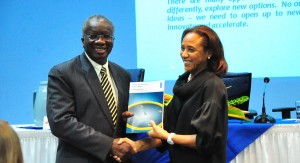 PM Stuart accepts a copy of the Human Development Report 2013 from UNDP Resident Rep. Michelle Gyles-McDonnough.