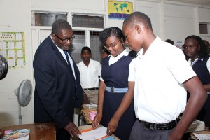 LET'S SEE YOUR WORK: Parliamentary Secretary in the Ministry of Education, Senator Harry Husbands and students of the Unique High School today.