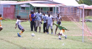 Belmont Primary's goalie Flourish Holder seeks to protect his goal bars from this St. Giles attack as spectators wait anxiously on the outcome.