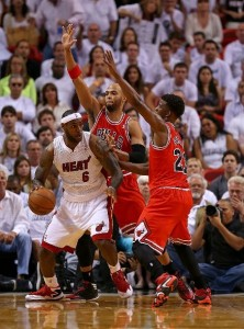 Heat's LeBron James (with ball) is double- teamed by Bulls' Taj Gibson and Jimmy Butler (right).