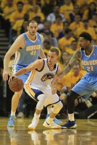 Warriors Stephen Curry (with ball) is defended by Nuggets' Wilson Chandler (right).