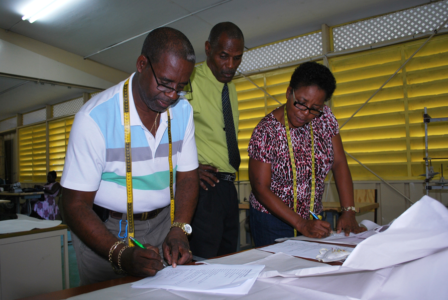 Tutor Timothy Howell (centre) with two of his Beginner's Tailoring students, Osmond Hoyte and Myrna Hayde, as they get drafting notes for the construction of a gent's long sleeved dress shirt.