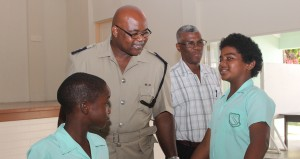 Senior Superintendent, Eucklyn Thompson and Milton Lynch Primary School teacher, Errol Bynoe talking to students Cadeem Knight and Dwayne Lewis.