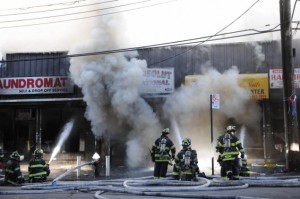 Firefighters battle a five-alarm fire on White Plains Road in the Bronx early today.