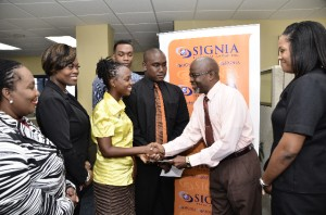 Commercial officer at Signia, Orrie Chandler presents a cheque to marketing specialist at Book Line, Cheneka Moore.