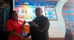 Garfield Callender of the National Award Council accepts paint supplies from Jennifer Husbands of Harris Paints.