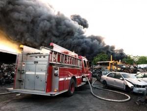 Smoke billows from scrap metal fire.