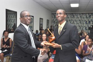 Rico Boyce collects the Michael Clarke award from the Barbados Association of Medical Practitioners head, Dr. Carlos Chase.