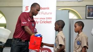 Kraigg Brathwaite (left) making presentations to members of St. Paul's Primary cricket team