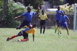 St. Bartholomew's Thierry Gale (blue shirt) jumps over this challenge from the A Dacosta Edwards Primary player.