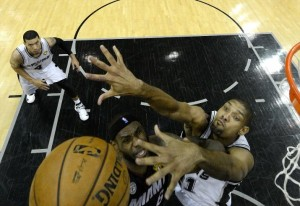 Spurs' Tim Duncan (right) challenges Heat's LeBron James' lay-up during last night's game.