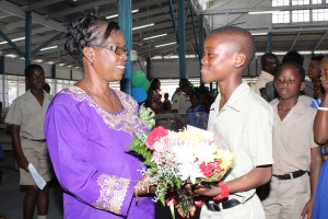 Past principal and honoured retiree Muareen Reid accepting a bouquet of flowers from headboy D'Andre White.