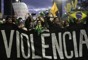 Demonstrators shout anti-government slogans behind a banner, during one of the many protest around Brazil yesterday.
