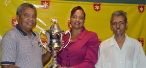 Sharron Alleyne-Elcock (centre) hands over the champion's trophy at stake in the Barbados Derby to Barbados Turf Club director Luther Miller (left) and liaison officer, Mohammed Mohamad.