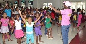 This is how we do it: A camp director giving some of the campers directions during a song session.