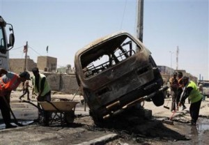 Street cleaners remove debris on the road at the site of a car bomb attack in Basra, southeast of Baghdad