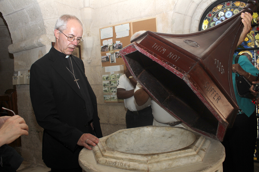 Archbishop Justin Welby looking at a 1684 baptism tower from the St. James Parish Church.