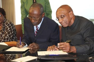 Sir Frank Alleyne (left) and Dr. DeLisle Worrell signing the MOU today.