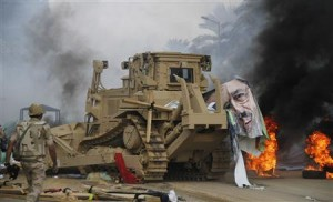 A poster of deposed Egyptian President Mohamed Mursi lies on a bulldozer around Cairo University and Nahdet Misr Square, where members of the Muslim Brotherhood and supporters of Mursi were camping in Giza