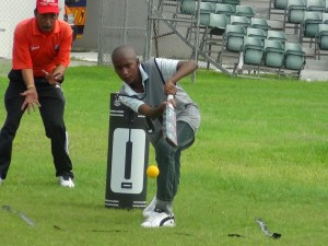 Coach Mohmad Pandor fields while a young participant tries to hit some targets.