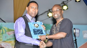 Minister of Culture, Sports and Youth, Stephen Lashley presents the 2013 Spouge Award to Malcolm Austin.
