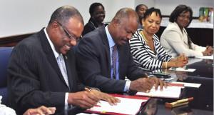 From left: Minister of Health John Boyce, Professor Hilary Beckles sign the MOU, while Deputy Principal Professor Eudine Barriteau looks on.