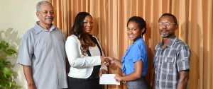Recipient/Scholarship Winner – Olivia Dos Santos  Receiving cheque from – Shontelle Murrell (Attorney-at-Law  of the law firm George Walton Payne & Co & the firm's representative on the Board of Trustees) Looking on – Father – Michael Dos Santos and Retired Permanent Secretary, Mr. Darwin Goodridge (The Secretary/Treasurer of the Trust)