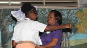 Retired teacher Coreen Campbell gets a hug from student Akayla Griffith.