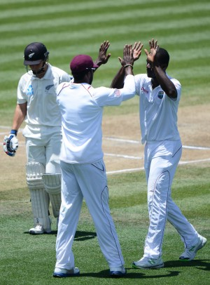 B.J. Watling walks away as Kirk Edwards and Darren Sammy celebrate his wicket on the third day of the third Test on Saturday at Seddon Park. (Photo courtesy WICB)