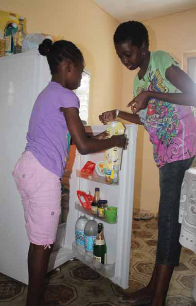 Were it not for help from her nine-year-old daughter Shania (left), Melissa Murray, who struggles with sickle cell anaemia would find it difficult to get items out of the refrigerator, among other things in the household.