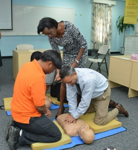 CEO of the Heart & Stroke Foundation of Barbados Inc, Gina Pitts going through the techniques of first aid with BL&P human resources manager, Roger Babooram during the employee training session.